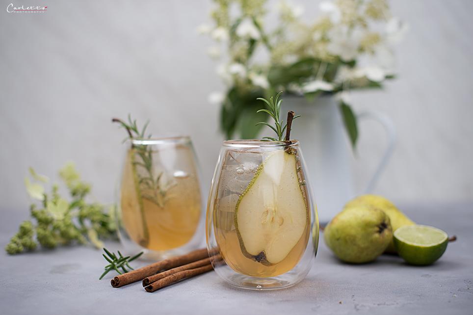 Cocktail mit Birnen und Gin auf grauem Untergrund, Birne, Zimtstange, Blumen in weißer Vase