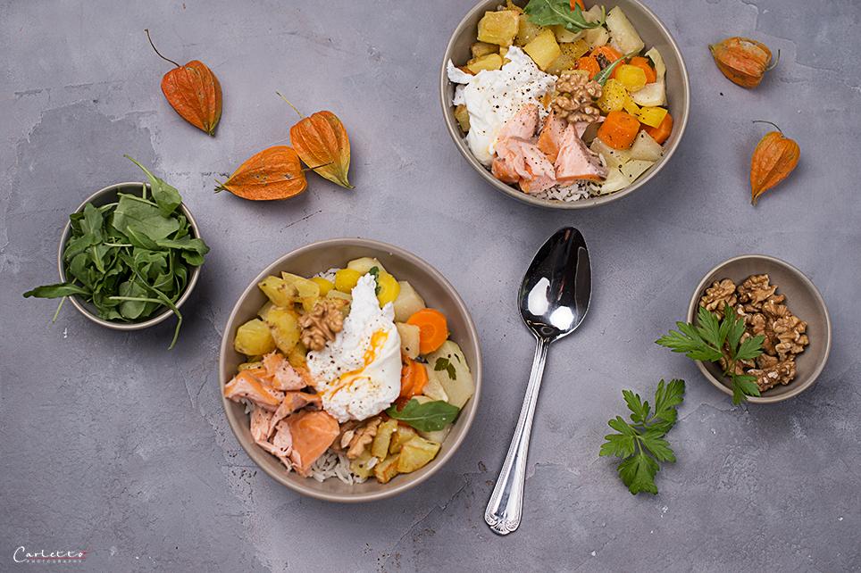 Schüsseln mit Reis. Gemüse, Lachs und pochiertes Ei, Rucolasalat