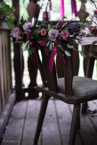 rustikaler Stuhl mit Blumengirlande in violett, Herbstdekoration