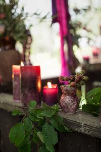 Kerzen in beerigen Farben mit Blättern, Herbstdekoration