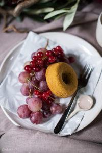 Donut auf Teller mit Weintrauben, Ribisel, Herbstdekoration