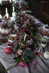 Tisch mit Blumengirlande, Kuchen, Beeren, Ästen, Herbstdekoration