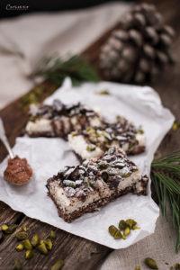 vegane Riegel mit Kokos, Pistazien, Schokolade auf einem Holzbrett mit Tannenzapfen