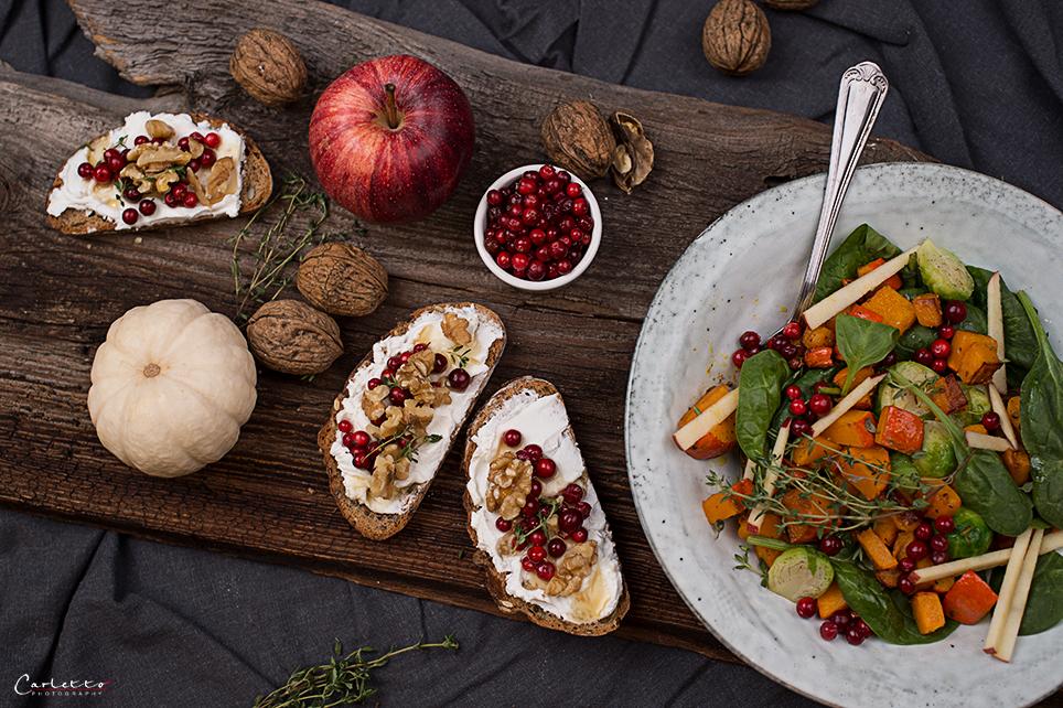 herbstlicher Salat mit Dressing und Brotscheiben mit Ziegenkäse, Nüssen und Preiselbeeren, Nüsse, auf grauem Teller mit braunem Hintergrund, Herbstsalat