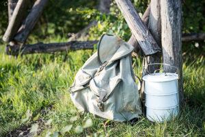 Rucksack neben Milchkanne auf Gras, Hochsitz, Rezepte zum Wandern
