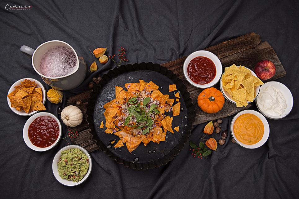 Tortilla Chips auf dunklem Teller mit Dips in Schüsseln, Tortilla Party