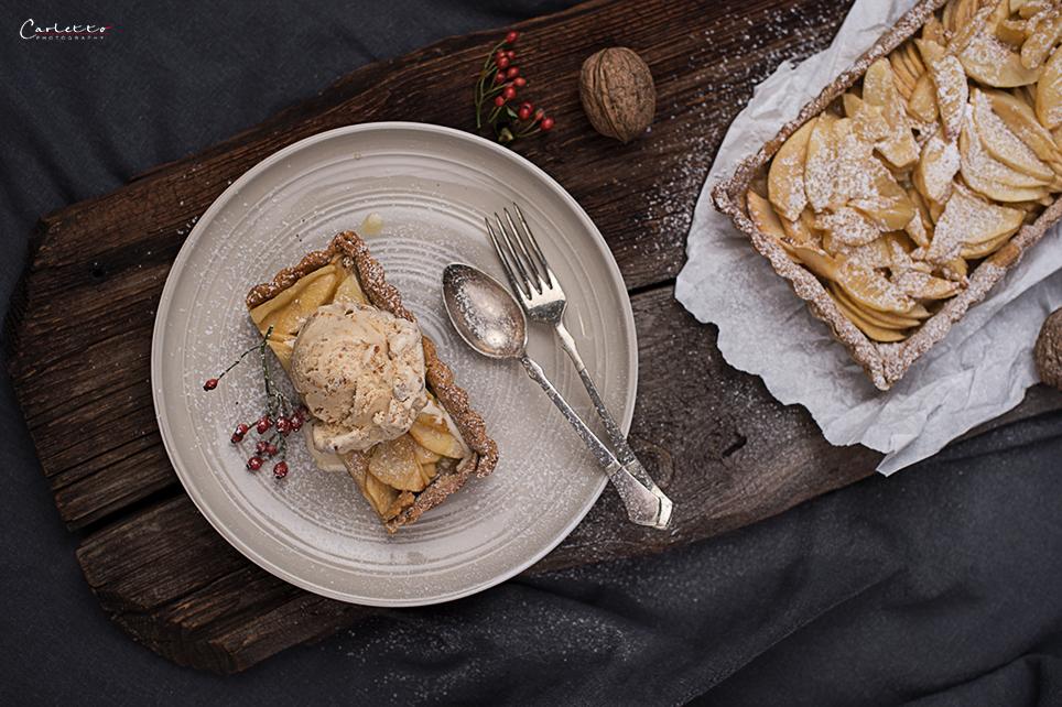 Herbstliche Apfeltarte aus Mürbeteig mit Spekulatiuseis, Nüssen auf einem Teller herbstlich dekoriert.