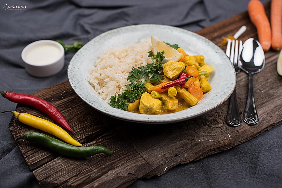 Klassisches Hühnercurry mit Karotten und Pfefferoni auf weißem Teller serviert.