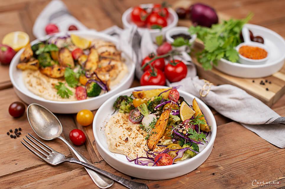 Hummus auf einem Teller serviert und mit bunten Gemuese dekoriert